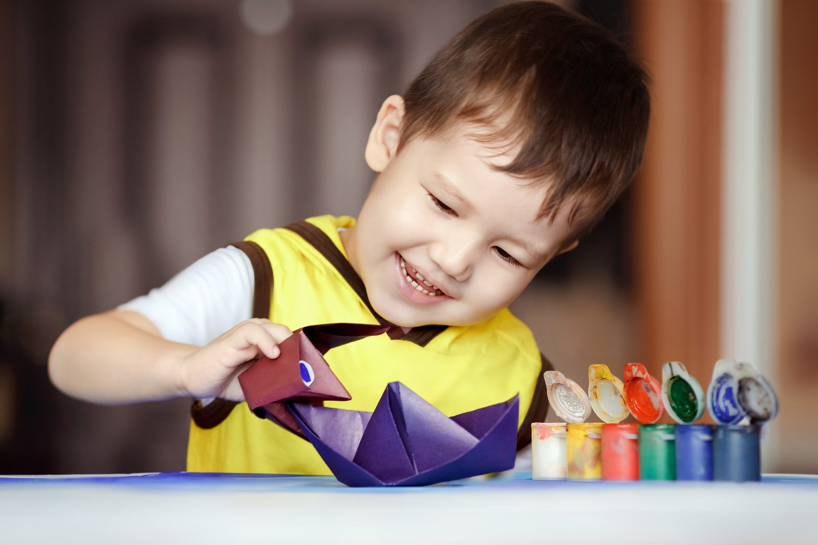 boy smiling while doing origami