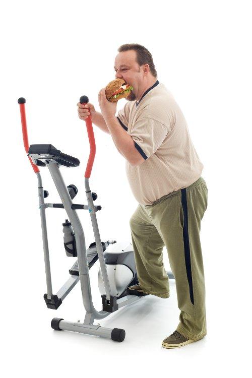 man using elliptical while eating a burger